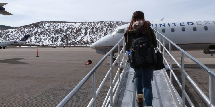 snowy mountains as girl boards a plane in Aspen, Colorado