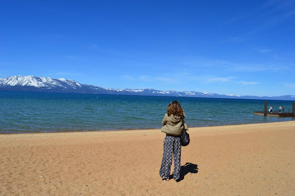 young girl in flowy pants reflecting looking at Lake Tahoe