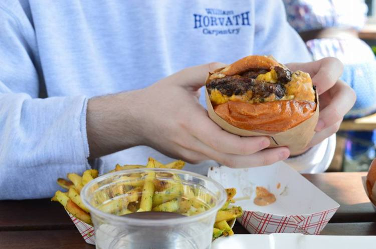 man-outside-holding-cheeseburger-fries