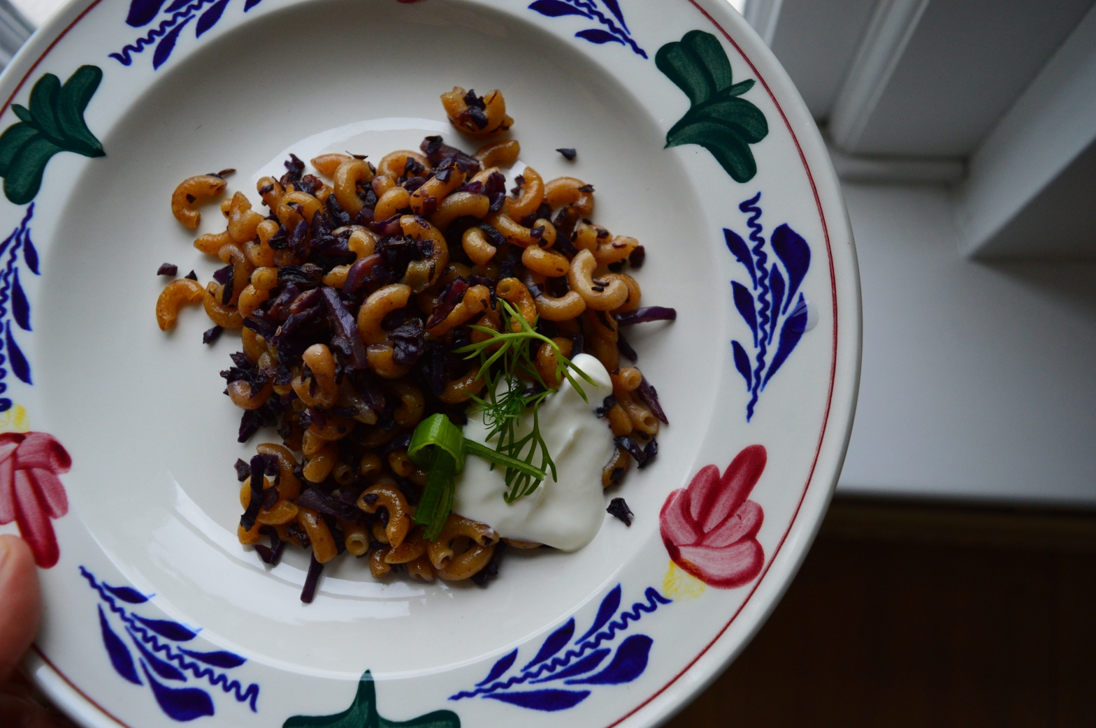 photo of a flower porcelain dish filled with purple cabbage, pasta, dill and greek yogurt