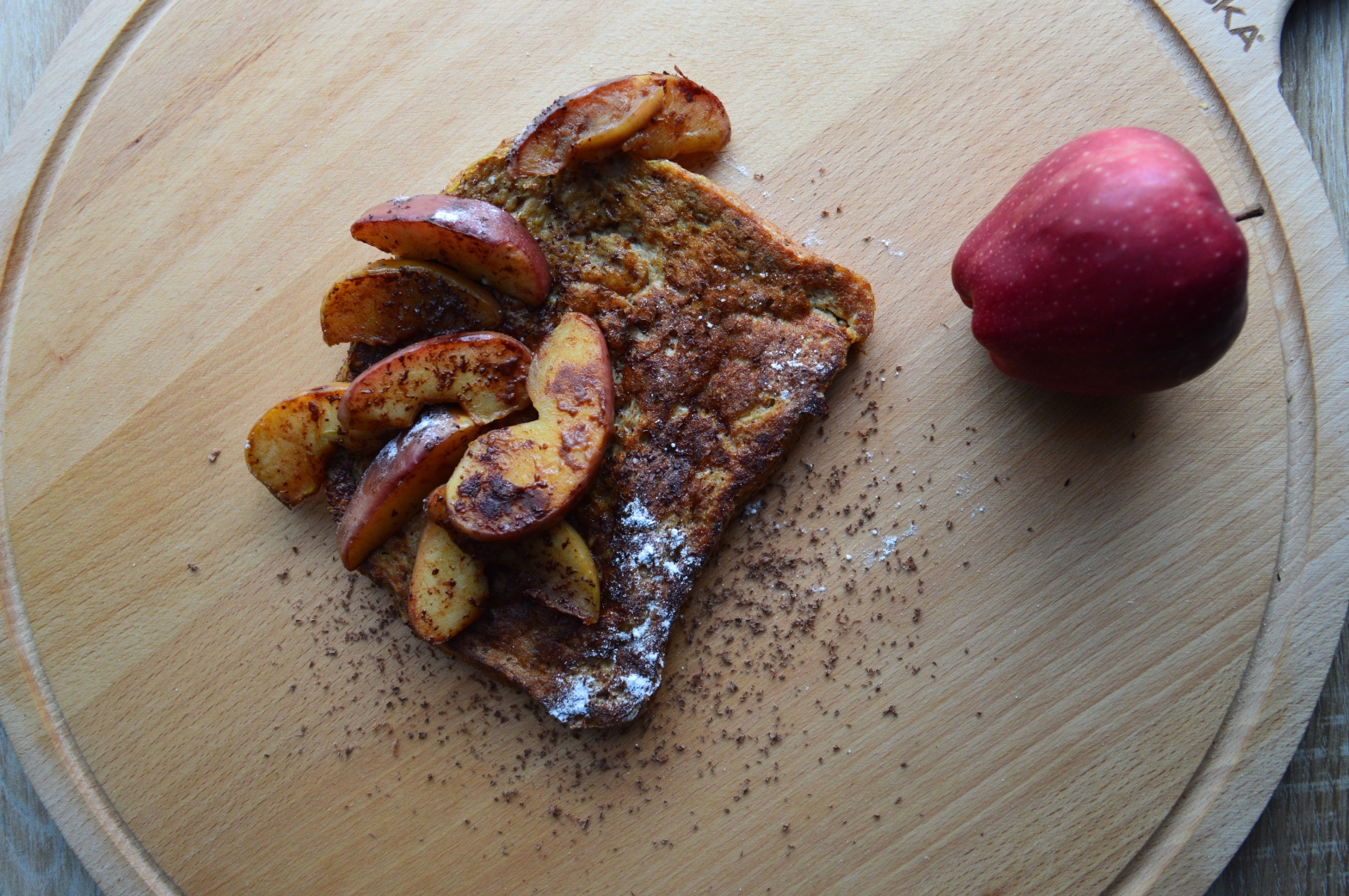 French toast on a wooden cutting board with sliced cinnamon apples and powdered sugar