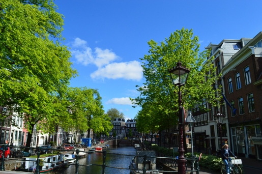 Woman biking on a sunny day on the canals of Amsterdam