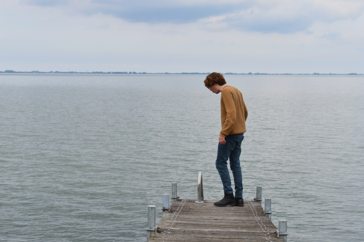man looking down at the water on a broken pier in the Netherlands on an overcast day