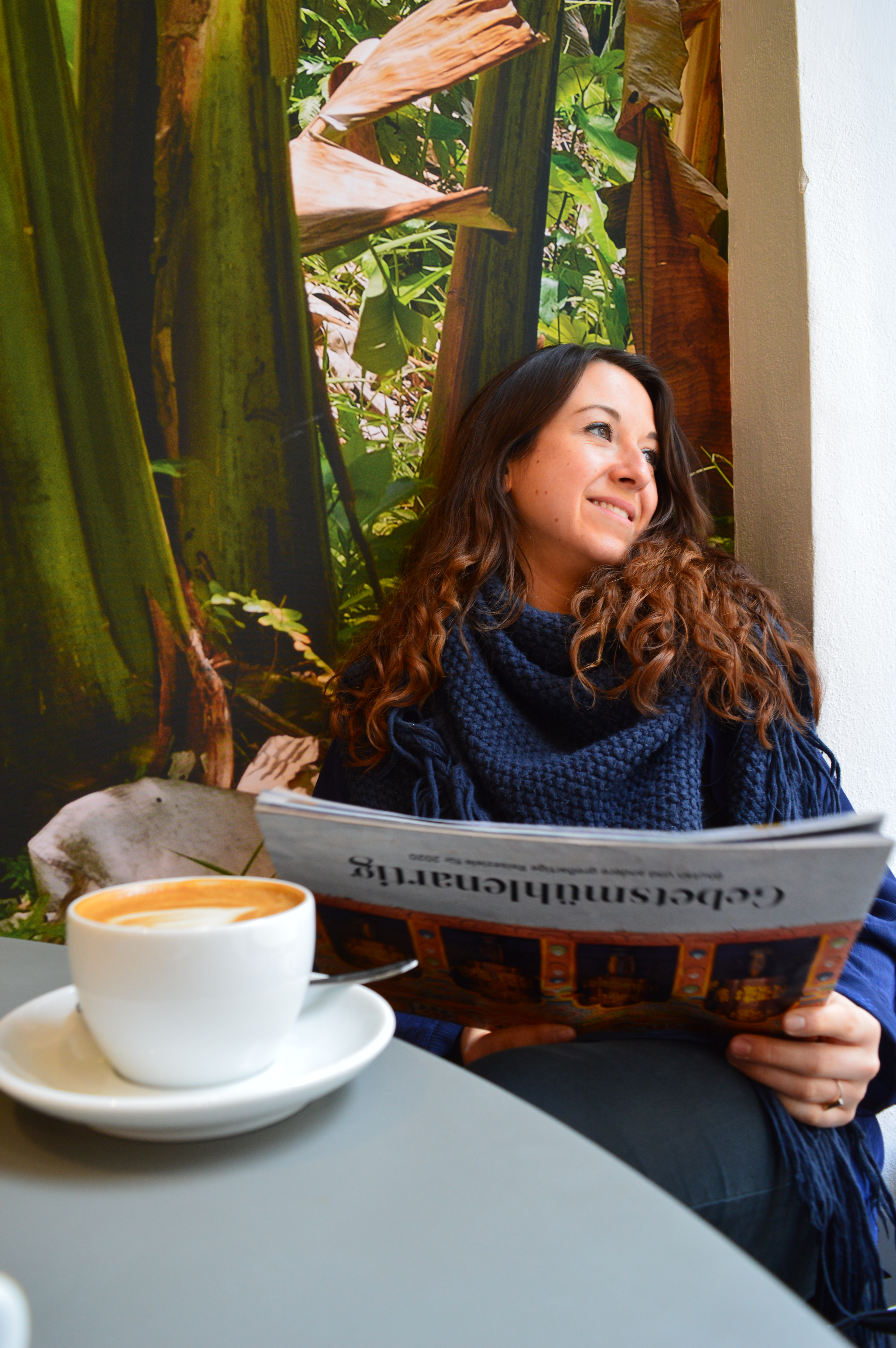 brunette sitting in a cafe in Vienna reading a newspaper with a coffee on the table