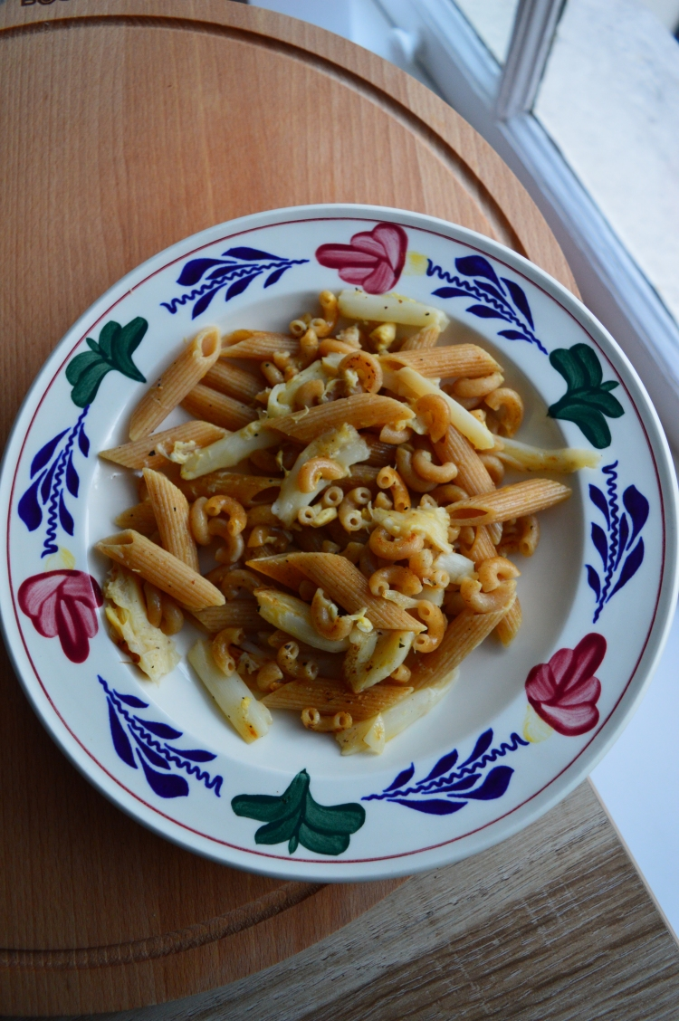 penne pasta with white asparagus in porcelain dish presented on wooden board