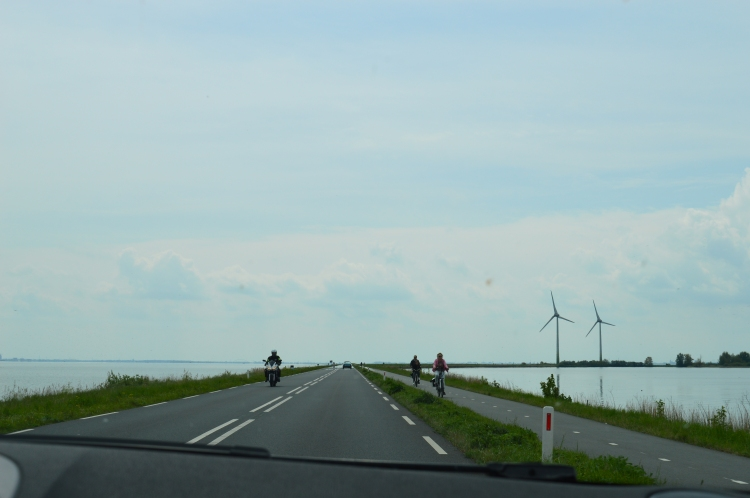 bike lane along the road in the Netherlands with windmills in the background