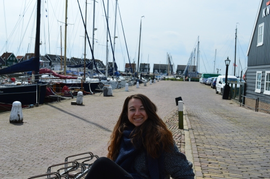 brunette girl smiling next to docks with sailboats in the Netherlands