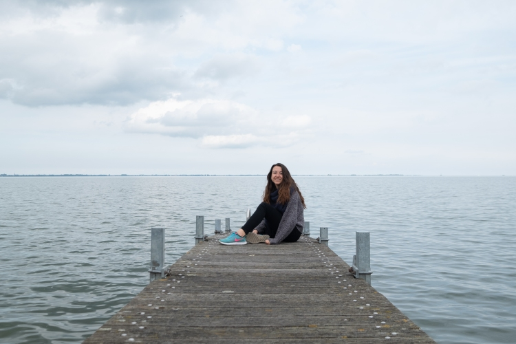 brunette girl sitting at the edge of a dock in the water on an overcast day