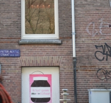 redhaired woman walking past a brick wall with graffiti and a nutella poster in Amsterdam