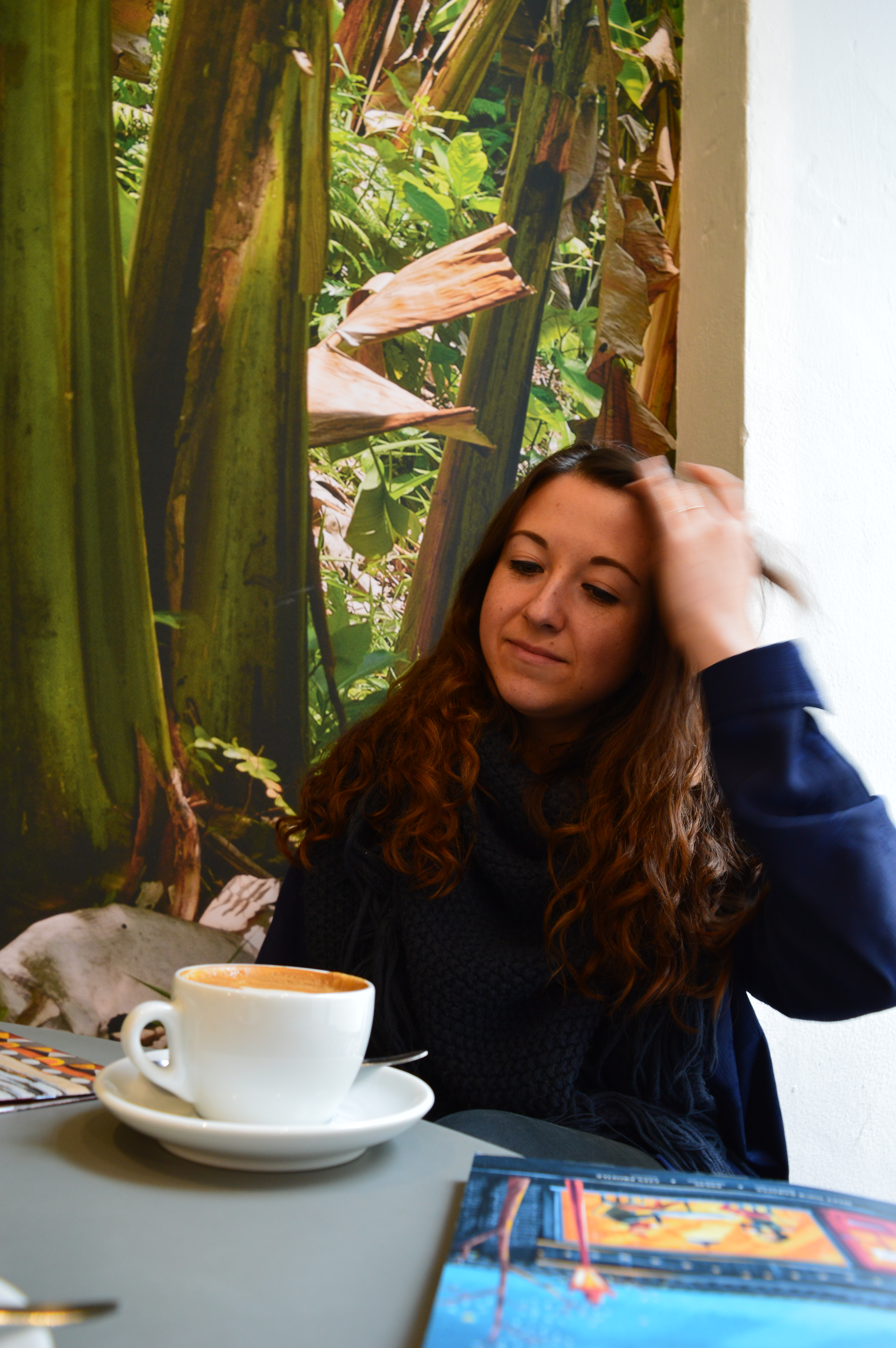 young, brunette girl touching her hair while sitting in a cafe with coffee in Vienna, Austria