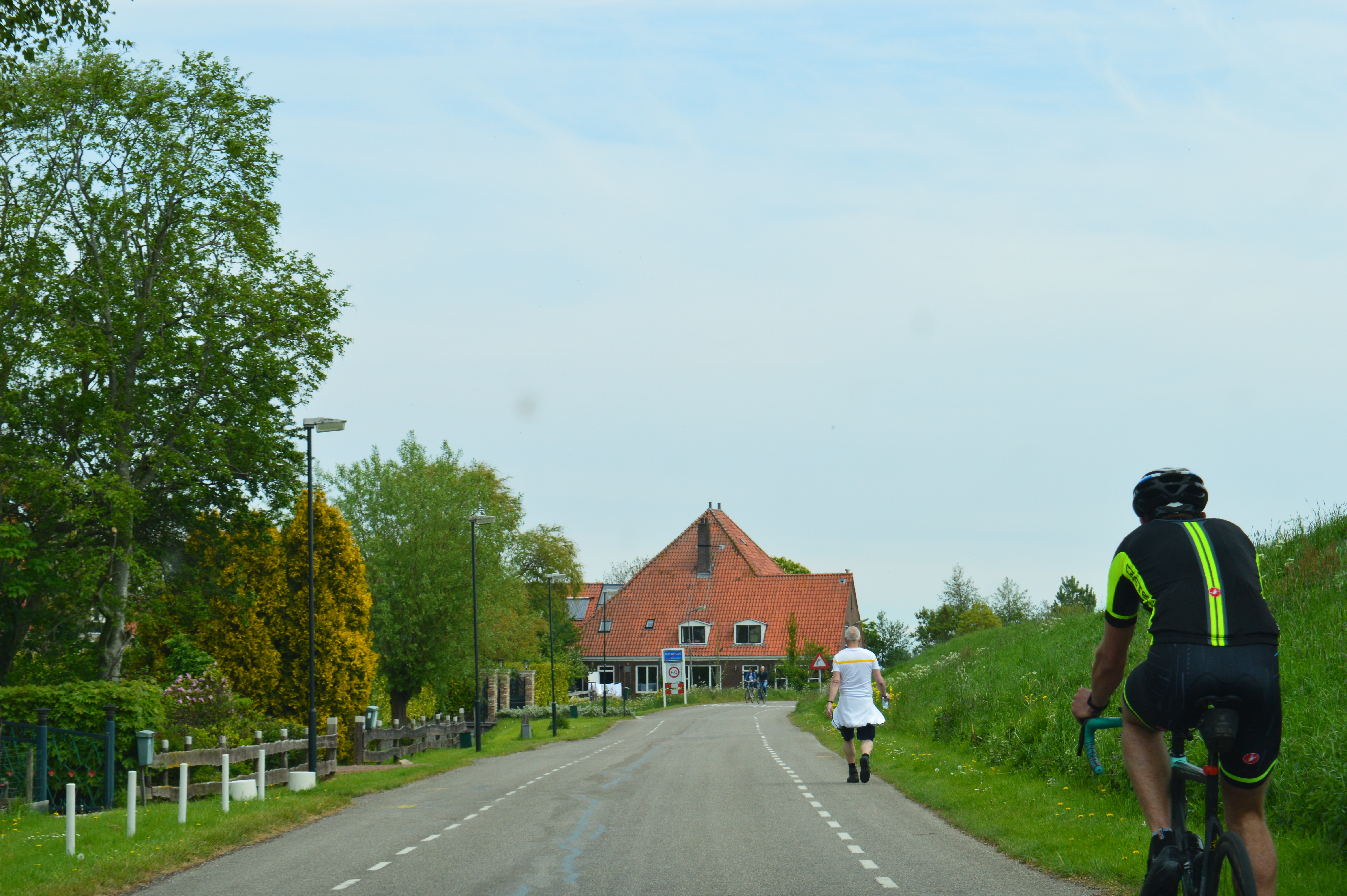 people walking and biking on the road in a small village in holland